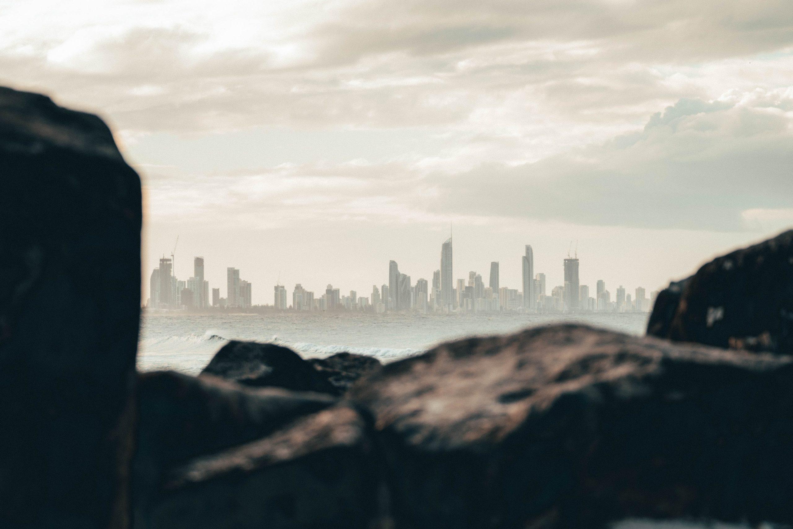 City and Buildings behind ocean rocks